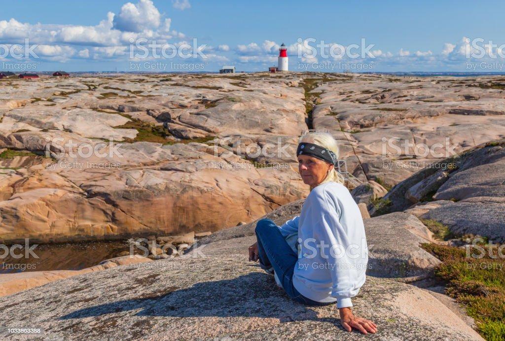 Senior woman sitting in front of the lighthouse on Hållö island near Smögen, Bohuslän on the Swedish west coast stock photo