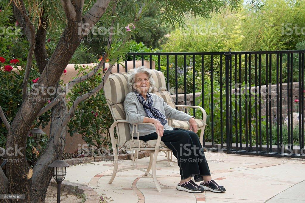 Senior Woman Sitting in Garden stock photo