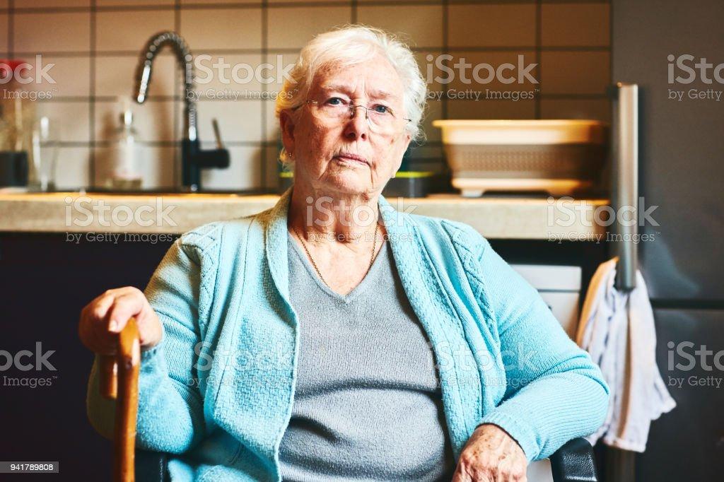 Senior woman sitting in kitchen stock photo