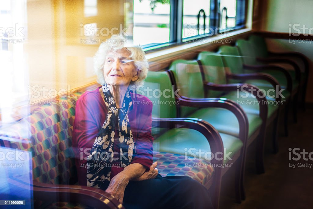 Senior woman sitting in waiting room at doctor office - foto stock