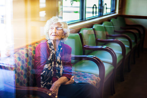 Senior woman sitting in waiting room at doctor office stock photo