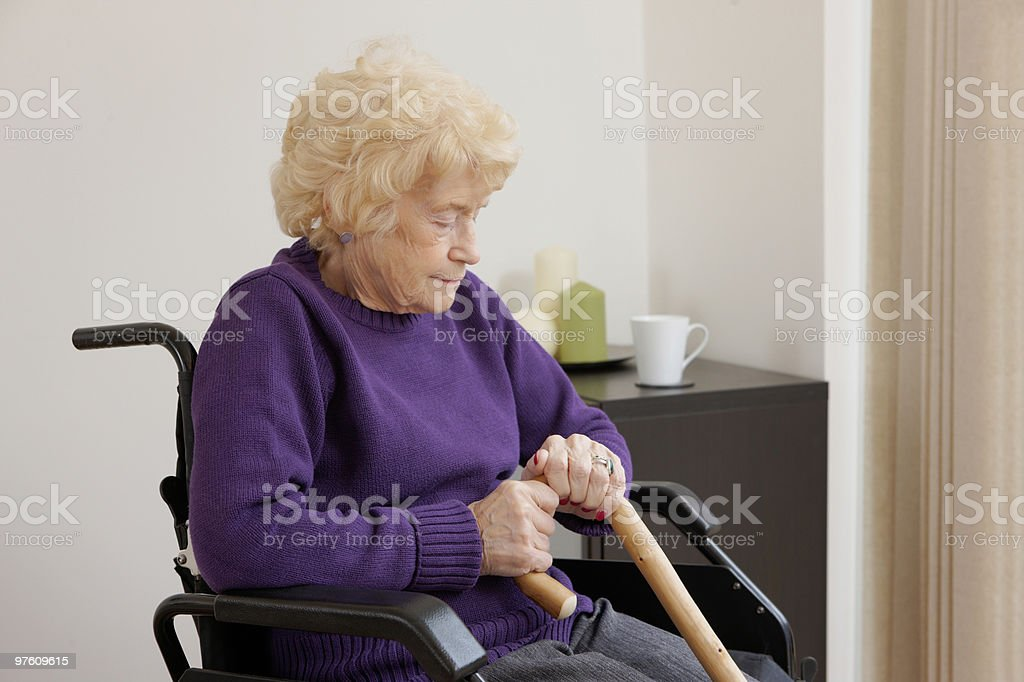 senior woman sitting in wheelchair at home royalty-free stock photo