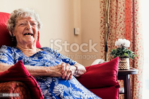 Senior woman laughing while sitting in an armchair in a nursing home in North East of England. She has her walking aid in front of her.