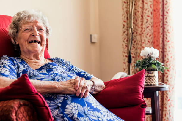 senior woman sitting laughing - fragile stock pictures, royalty-free photos & images