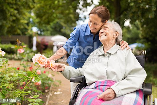 istock Senior woman sitting on a wheelchair with caregiver 543455614