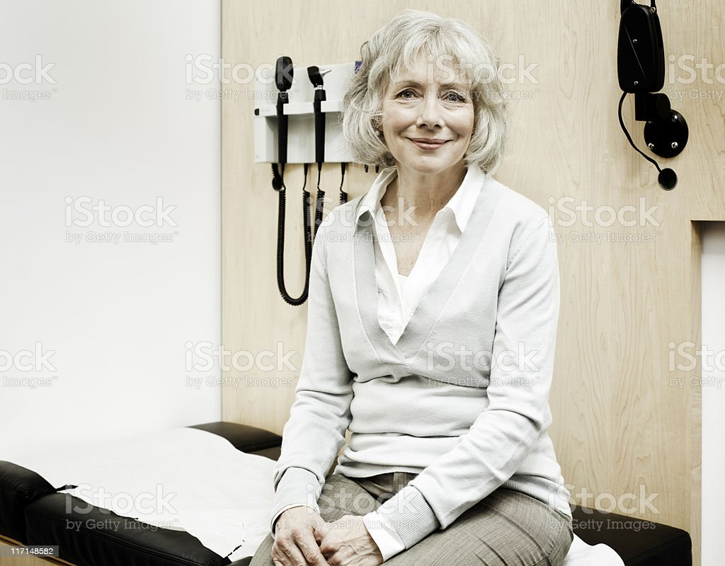Senior Woman Sitting on an Examination Table stock photo