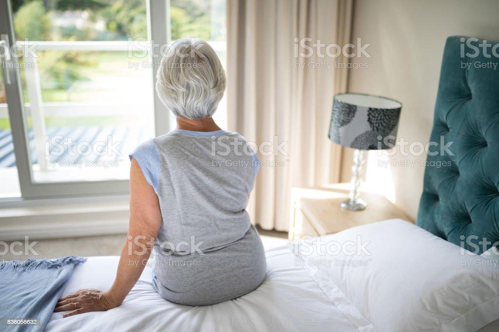 Ältere Frau sitzt am Bett im Schlafzimmer – Foto
