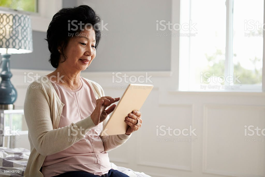 Senior Woman Sitting On Bed Using Digital Tablet stock photo