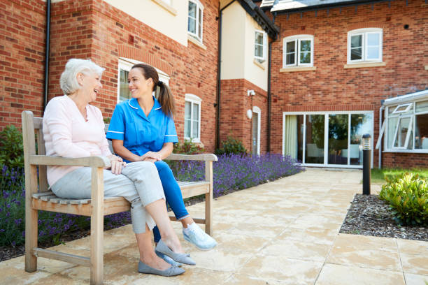 Senior Woman Sitting On Bench And Talking With Nurse In Retirement Home Senior Woman Sitting On Bench And Talking With Nurse In Retirement Home retirement community stock pictures, royalty-free photos & images