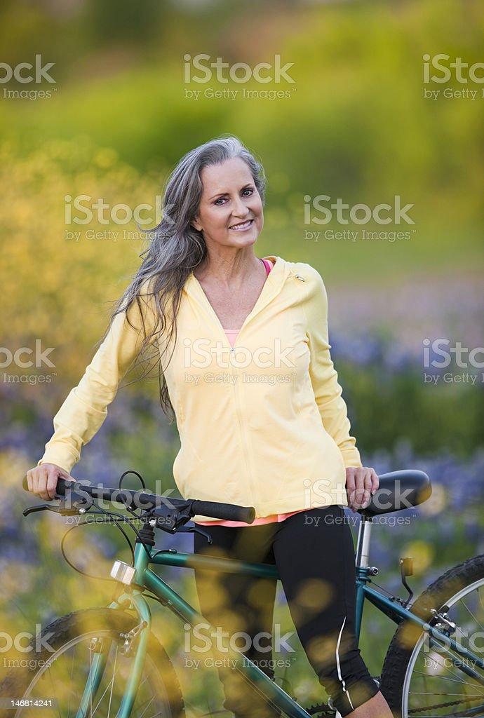 Senior Woman Sitting On Bicycle In Bluebonnet Field royalty-free stock photo