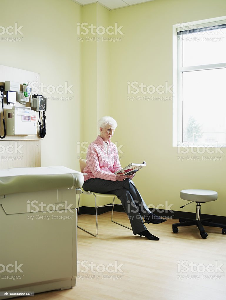 Senior woman sitting on chair in exam room reading magazine foto de stock royalty-free