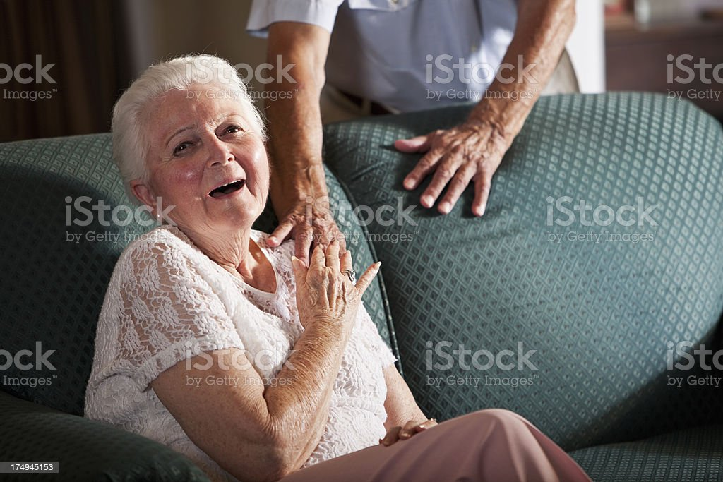 Senior woman sitting on couch, laughing royalty-free stock photo