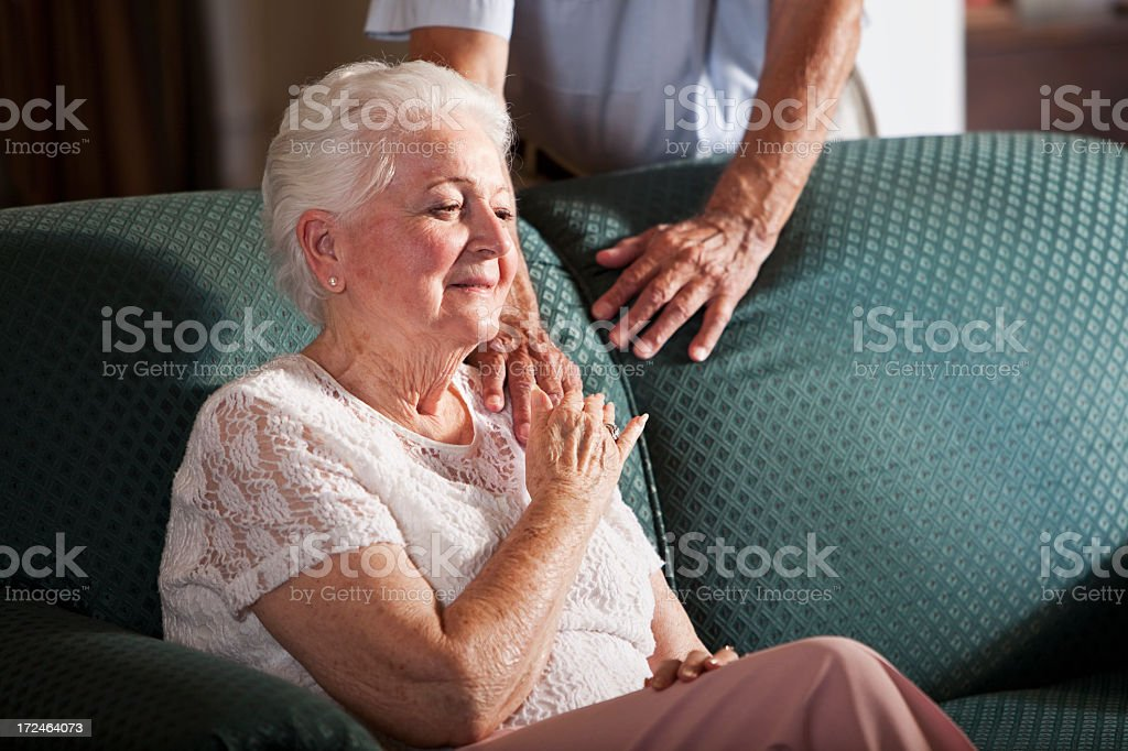 Senior woman sitting on couch stock photo