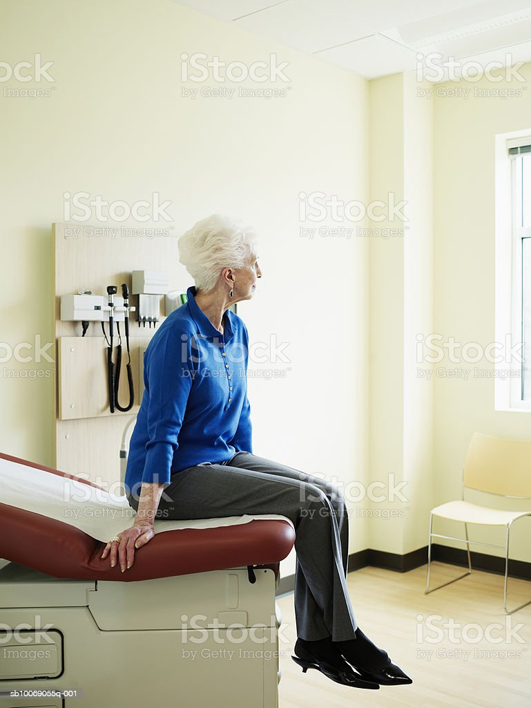 Senior woman sitting on examination table, looking away foto de stock royalty-free