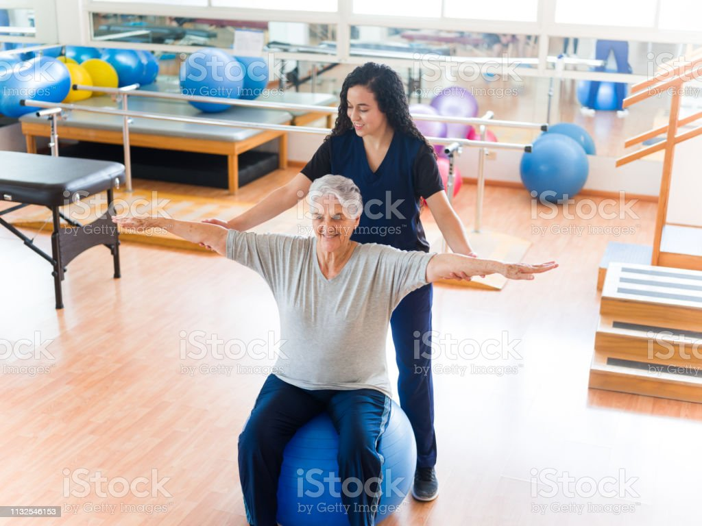 Senior Woman Sitting On Fitness Ball In A Phisica Therapy Room Stock Photo Download Image Now Istock