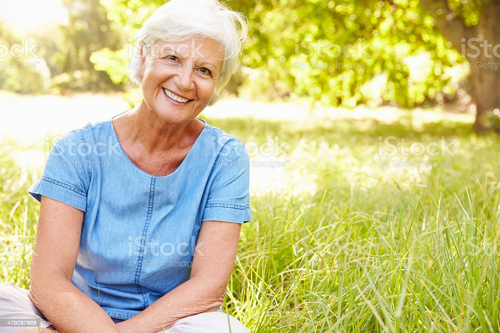 Senior woman sitting on grass relaxing stock photo