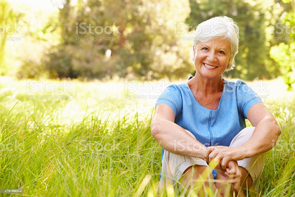 Senior woman sitting on grass relaxing, smiling to camera stock photo
