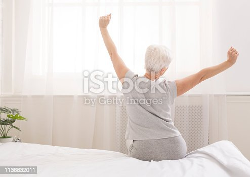 Senior woman sitting on her bed in morning, stretching with arms raised, back view, free space