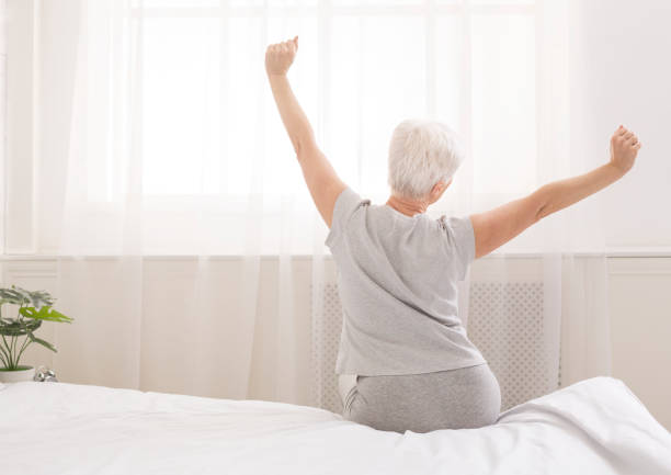 Senior woman sitting on her bed in morning stock photo
