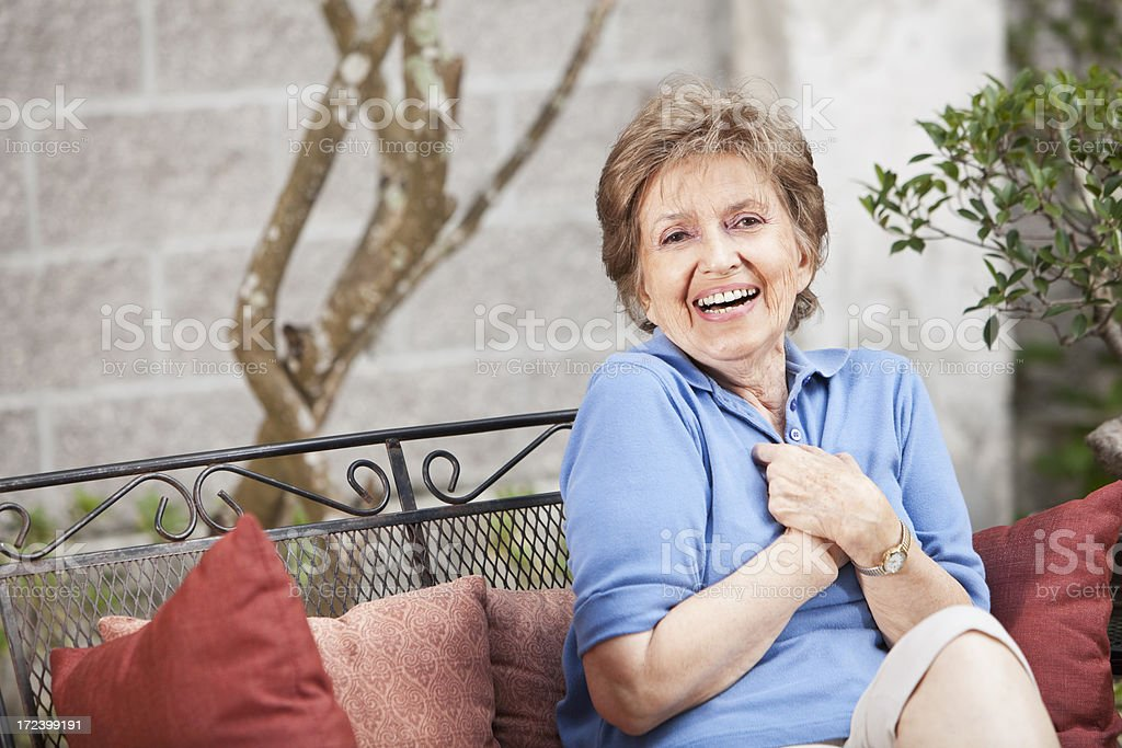 Senior woman sitting on patio stock photo