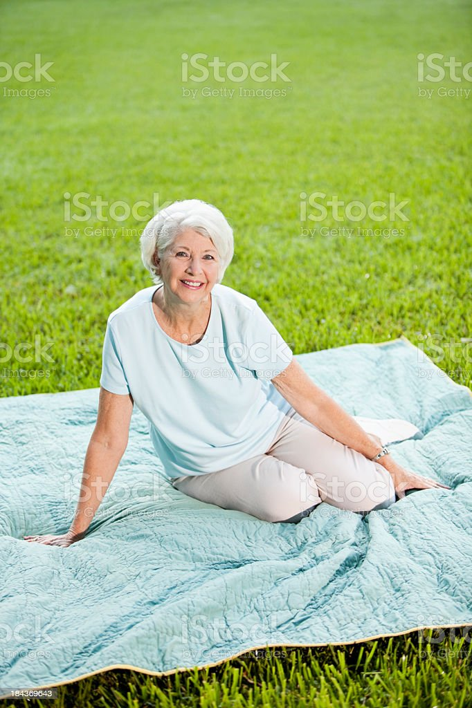 Senior woman sitting on picnic blanket stock photo