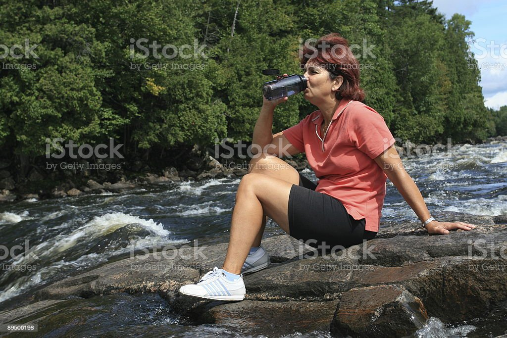 Senior Woman Sitting on Rock in River and Drinking Water 免版稅 stock photo