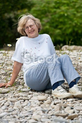 A senior woman sitting on a rocky beach, looking towards the camera.