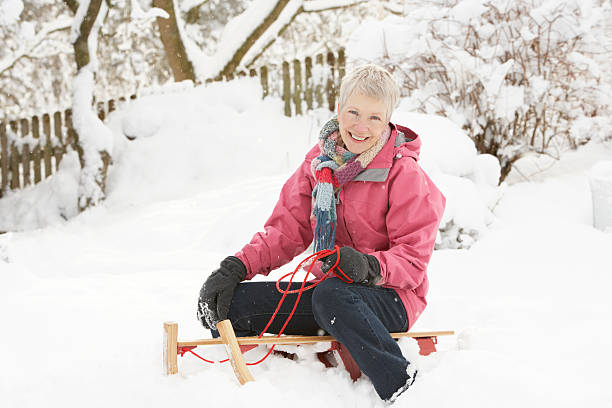 Senior Woman Sitting On Sledge In Snowy Landscape stock photo