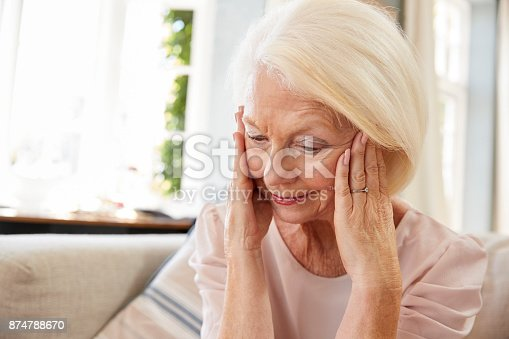 874789168istockphoto Senior Woman Sitting On Sofa At Home Suffering From Depression 874788670