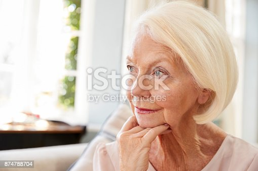 874789168istockphoto Senior Woman Sitting On Sofa At Home Suffering From Depression 874788704