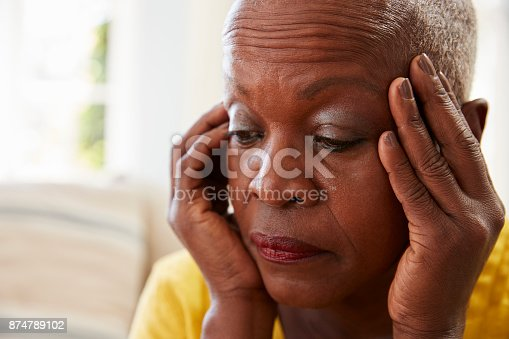 874789168istockphoto Senior Woman Sitting On Sofa At Home Suffering From Depression 874789102