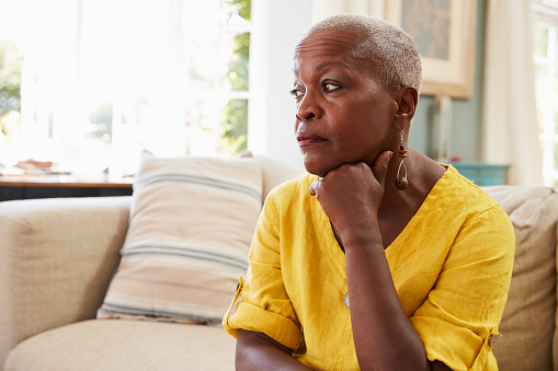 874789168 istock photo Senior Woman Sitting On Sofa At Home Suffering From Depression 874789168