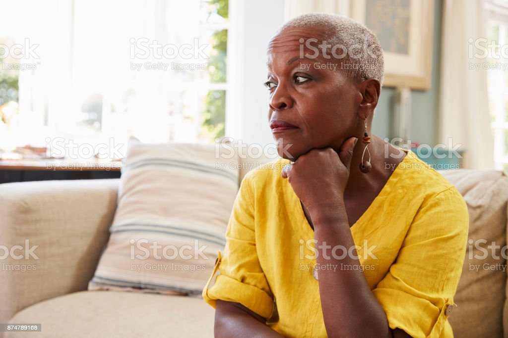 Senior Woman Sitting On Sofa At Home Suffering From Depression stock photo