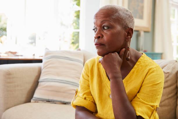 senior vrouw zitten thuis op bank lijden aan depressie - vrouw verdrietig stockfoto's en -beelden