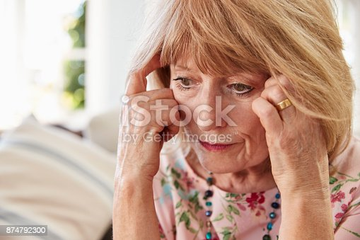 874789168istockphoto Senior Woman Sitting On Sofa At Home Suffering From Depression 874792300