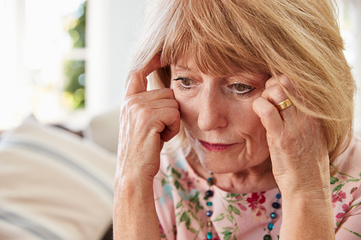 874789168 istock photo Senior Woman Sitting On Sofa At Home Suffering From Depression 874792300