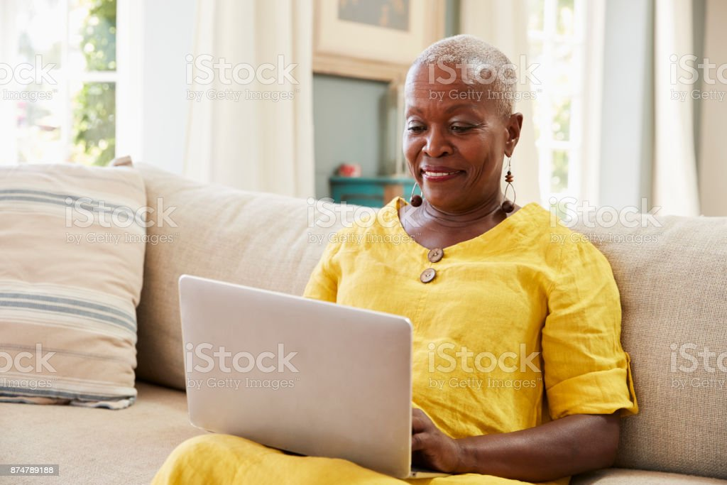Senior Woman Sitting On Sofa Using Laptop At Home Together stock photo