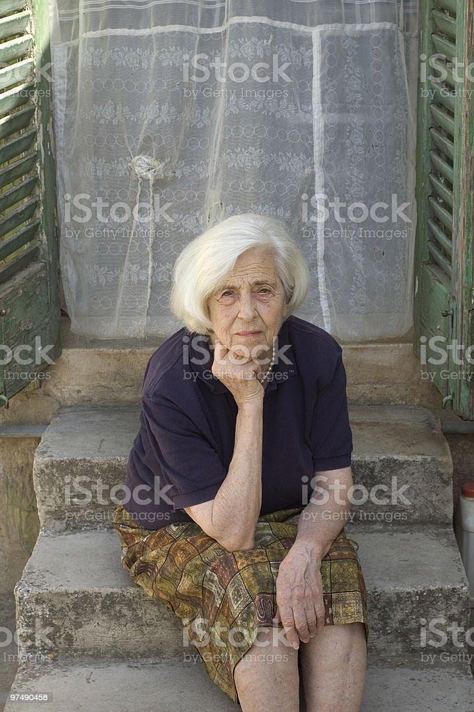 senior woman sitting on stairs royalty-free stock photo
