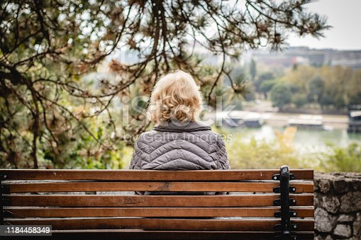 Lonely senior woman is sitting on the bench in park