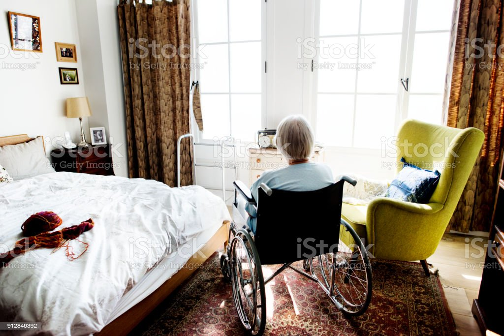 Senior woman sitting on the wheelchair alone stock photo