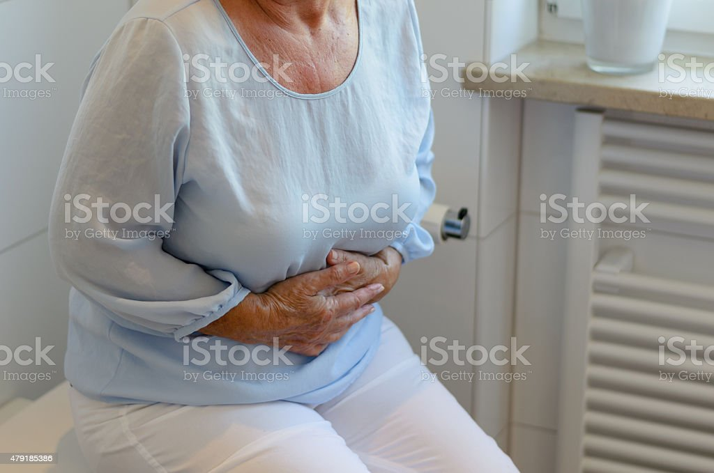 Senior woman sitting on toilet stock photo