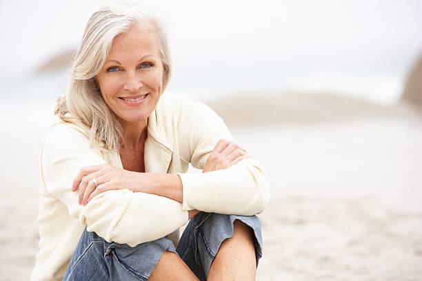 Senior Frau sitzt am Winter-Strand – Foto