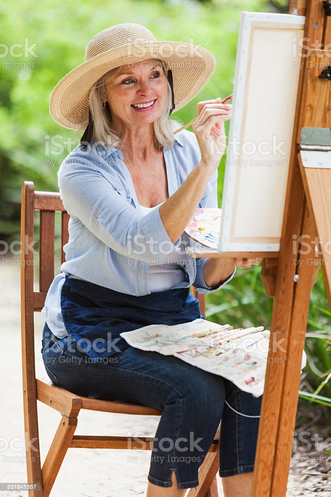 Senior woman sitting outdoors, painting stock photo