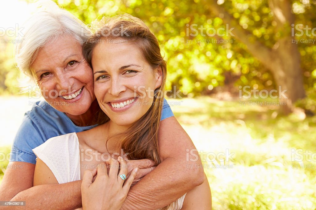 Senior woman sitting outdoors with her adult daughter stock photo