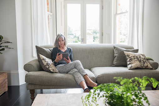 Senior woman sitting relaxing on the sofa using digital tablet