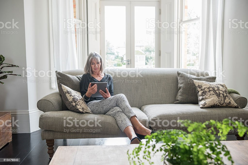 Senior woman sitting relaxing on the sofa using digital tablet stock photo