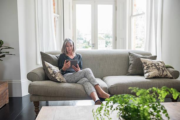 senior woman sitting relaxing on the sofa using digital tablet - vrouw 60 stockfoto's en -beelden