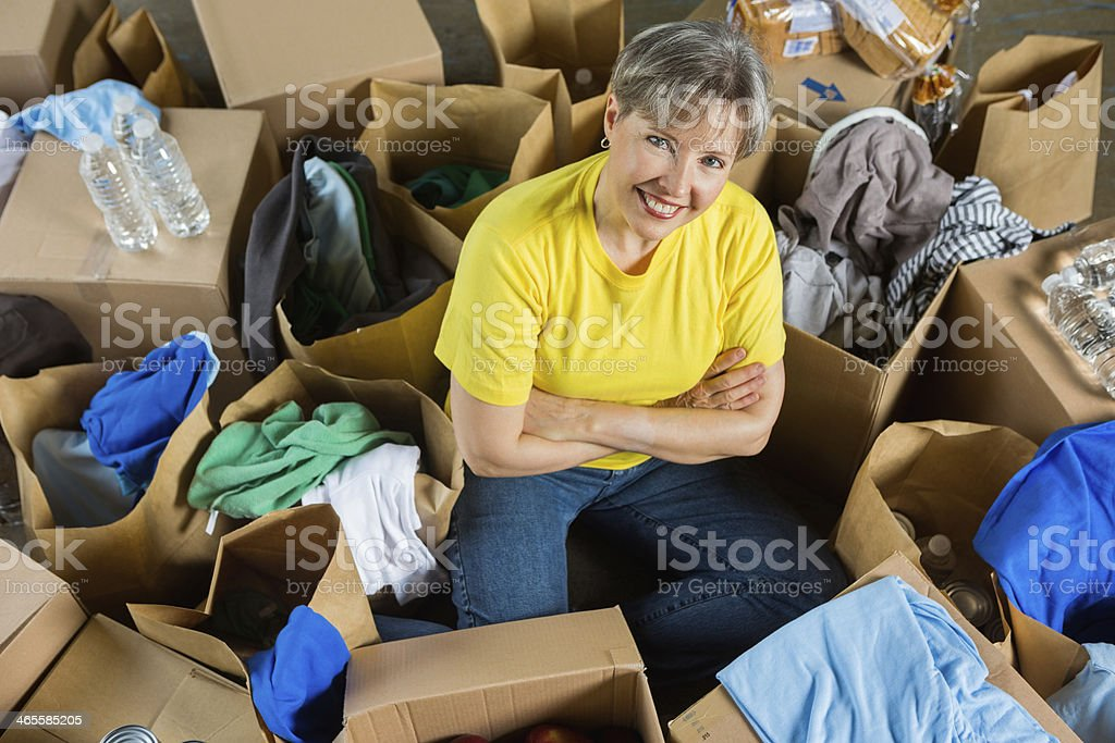 Senior woman sitting with boxes of clothing and food donations royalty-free stock photo