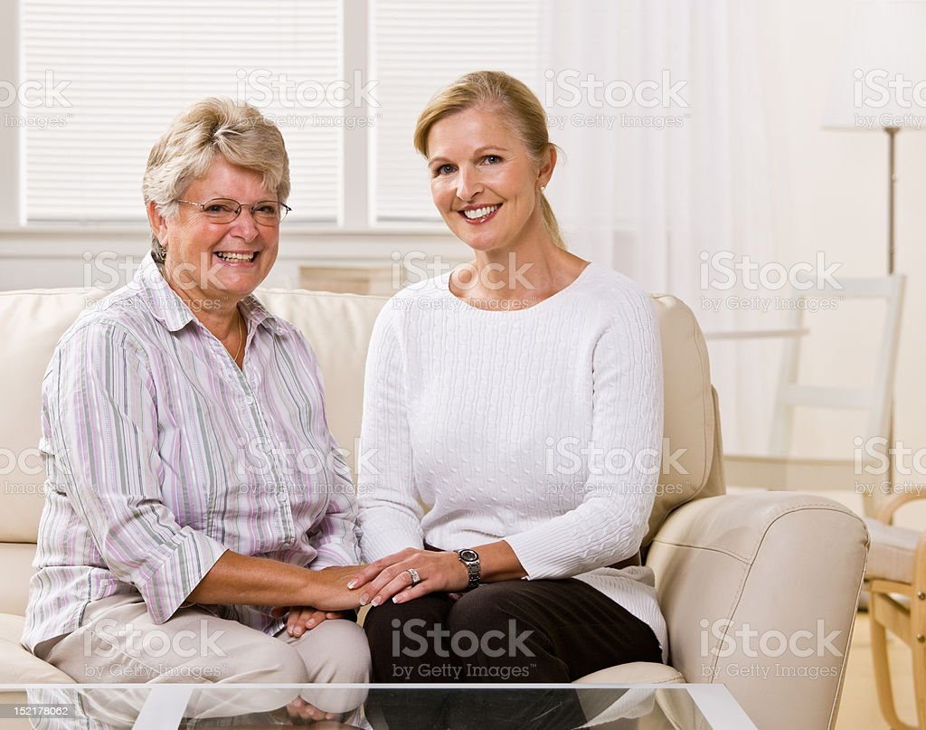 Senior woman sitting with daughter in livingroom royalty-free stock photo