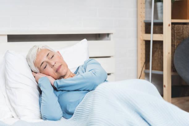 Senior woman sleeping on bed stock photo
